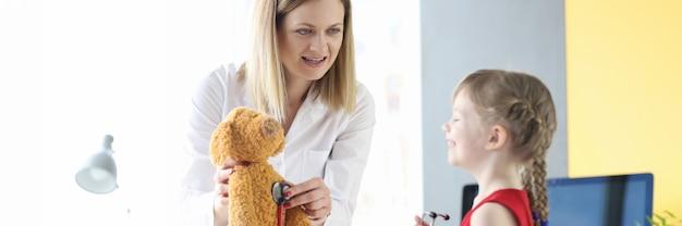 Bambina che ascolta l'orso giocattolo con lo stetoscopio insieme alla diagnosi medica dell'infanzia