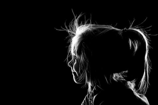 Bambina che osserva nell'oscurità