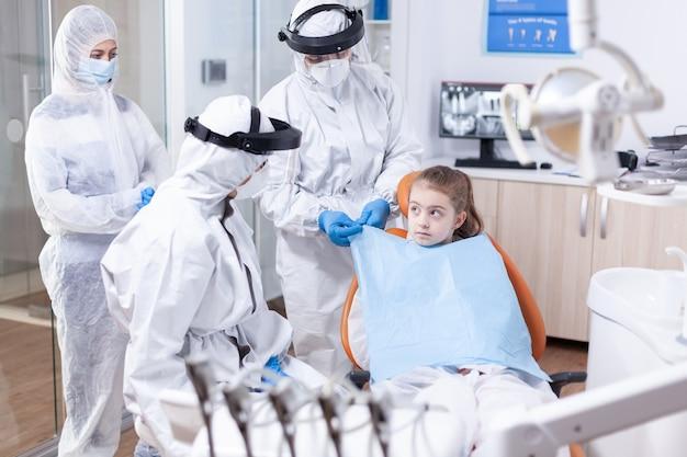 Bambina che guarda il dentista mentre l'assistente le sta mettendo un bavaglino prima dell'esame dentistico durante la pandemia di coronavirus. stomatologo durante il covid19 che indossa una tuta in dpi facendo la procedura dei denti del bambino s