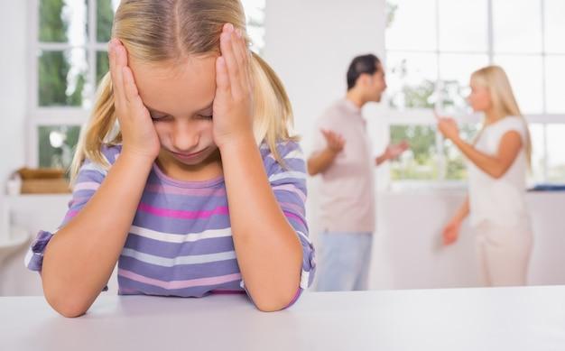 Bambina che sembra depressa davanti ai genitori combattenti