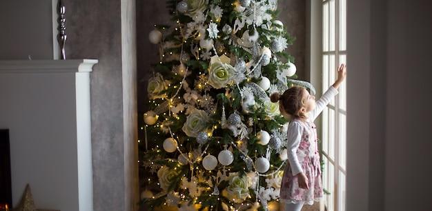 Una bambina guarda fuori da una grande finestra vicino a un albero di natale. aspettando un miracolo, decorazioni natalizie bianche nel soggiorno di casa. anno nuovo, fiaba e magia, sogni dei bambini