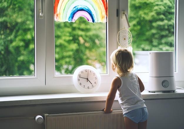 La bambina guarda fuori dalla finestra in primavera bambino carino sullo sfondo del dipinto arcobaleno sulla finestra