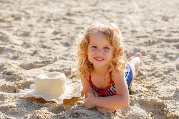 Bambina sdraiata sulla spiaggia in estate di sabbia