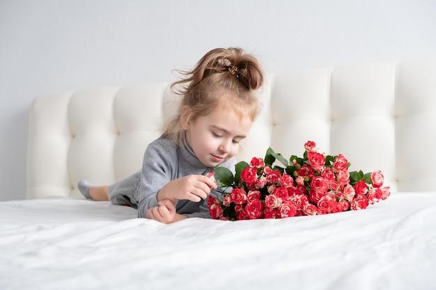 Bambina sdraiata sul letto con bouquet di rose rosa.