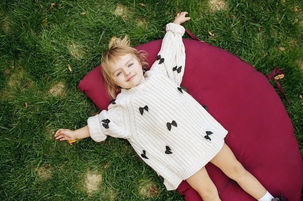 Bambina sdraiata sull'erba in giardino. pose del bambino femminile sul prato inglese sul cortile. kid divertirsi nel parco giochi all'aperto, infanzia felice