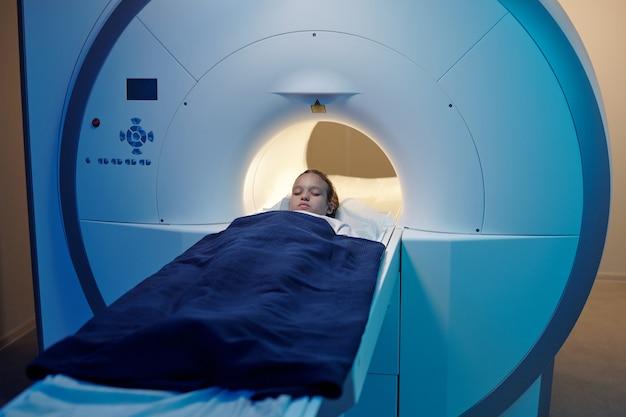 Bambina sdraiata su un lungo tavolo medico mentre si sposta nella macchina per la risonanza magnetica