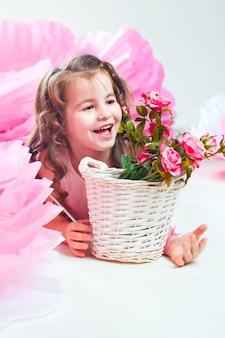 Bambina che si trova vicino al canestro con fiori di rosa