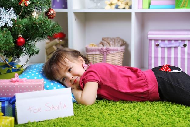 Bambina sdraiata vicino all'albero di natale nella stanza