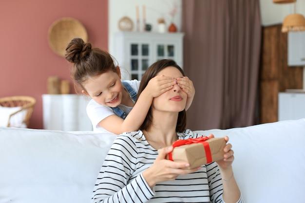 La bambina fa il regalo di compleanno al genitore eccitato, il bambino sorridente si congratula con la confezione regalo per la madre felice e gli occhi chiusi della madre.