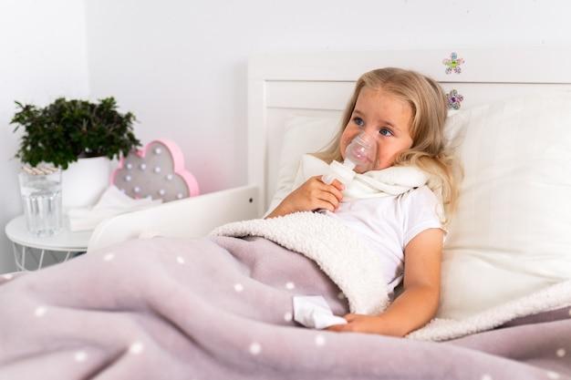 La bambina fa l'inalazione con un nebulizzatore in casa sdraiata a letto nella stanza bianca.