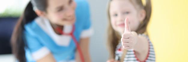 La bambina fa il gesto del pollice in alto all'appuntamento dal medico