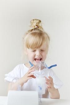 Bambina in una maschera per inalazioni, facendo inalazione con nebulizzatore a casa inalatore sul tavolo, coperta, bambino malato