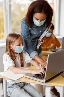 Bambina in maschera che utilizza laptop durante la lezione