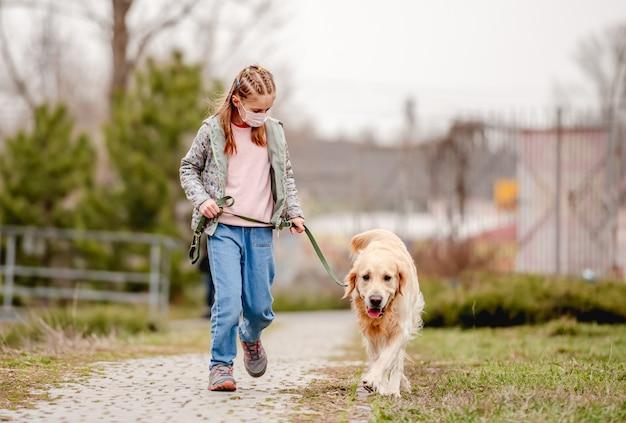 Bambina in maschera con cane golden retriever