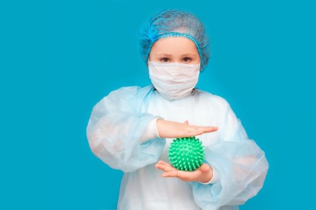 Una bambina con una maschera medica e un'uniforme tiene il coronavirus su sfondo blu