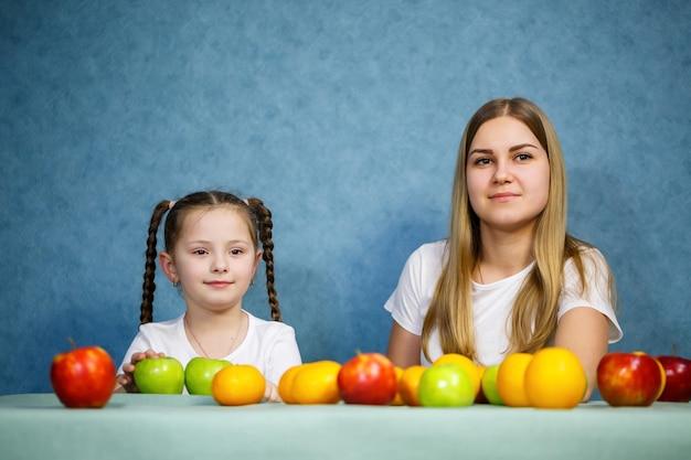 La bambina e la mamma giocano con la frutta e scherzano. indossano magliette