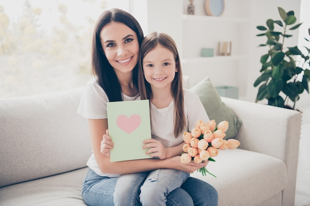La mamma della bambina che si siede sul divano accogliente in casa al chiuso tiene i fiori della cartolina presente dell'8 marzo