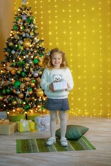 Bambina vicino all'albero di natale che tiene un regalo sorridente