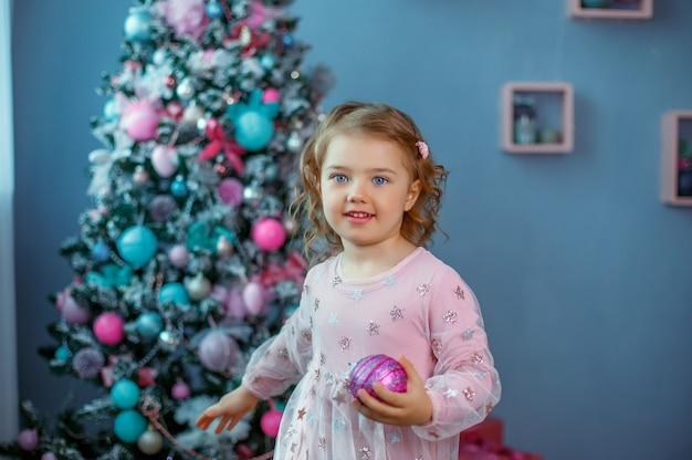 Una bambina vicino all'albero di natale tiene una palla di natale