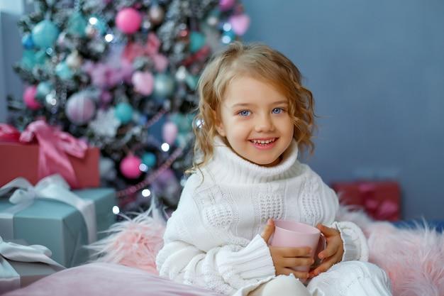 Una bambina vicino all'albero di natale tiene una tazza di tè caldo