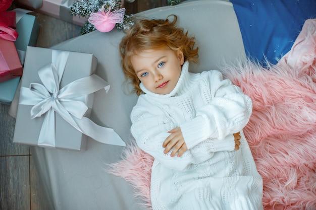 Una bambina vicino all'albero di natale è sdraiata sul letto