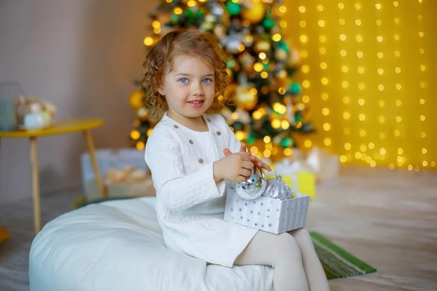 Bambina vicino all'albero di natale che gioca con i giocattoli di natale
