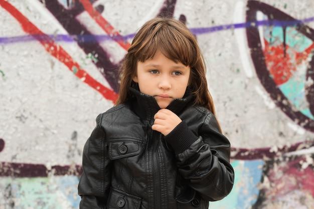 Bambina vicino al muro di graffiti