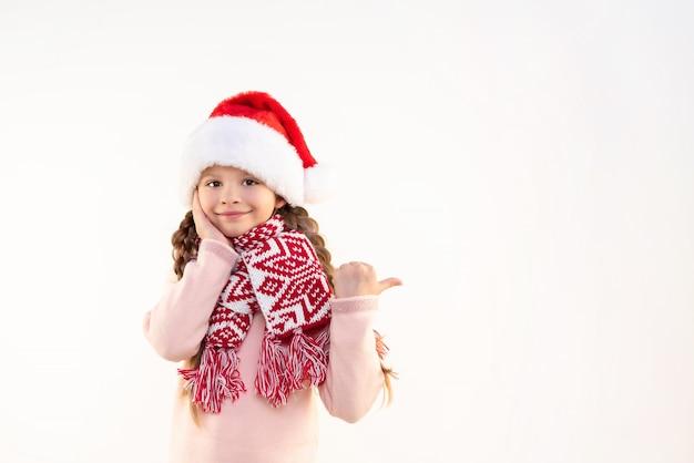 Una bambina con il cappello di capodanno punta il dito contro l'annuncio.