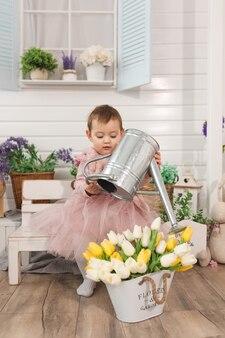 Bambina di un anno gioca nel cortile con annaffiatoio in metallo annaffiatoio tulipani fiori concetto di attività del tempo libero per i bambini