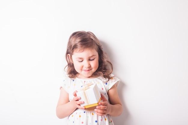 La bambina apre una confezione regalo con il presente. momento felice per il piccolo bambino