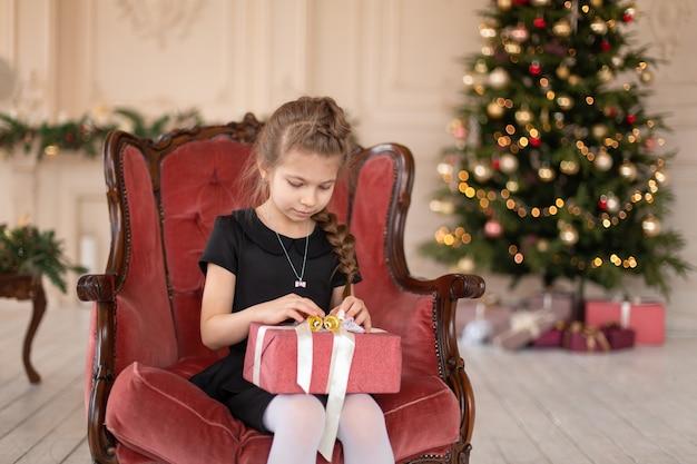 Una bambina apre un regalo di natale da babbo natale. racconto di natale. infanzia felice.
