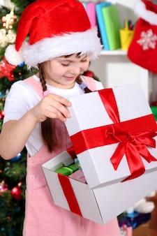 Una bambina apre un regalo in una stanza addobbata a festa
