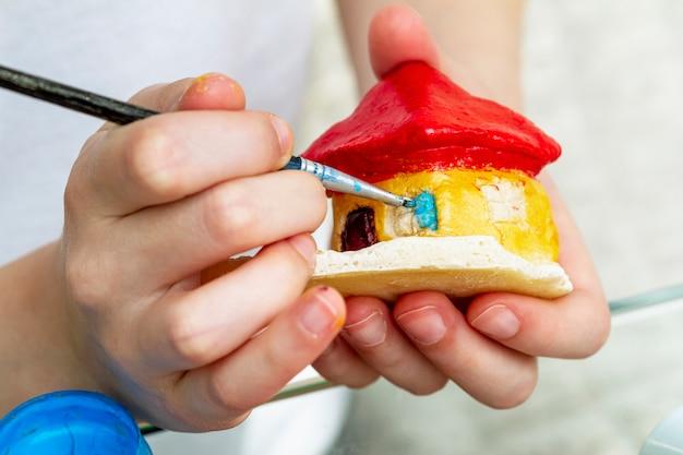 La bambina dipinge la casa dall'argilla o dall'impasto salato con colori acrilici. concetto di educazione.