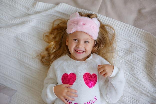 Bambina in pigiama sdraiato sulla vista dall'alto del letto