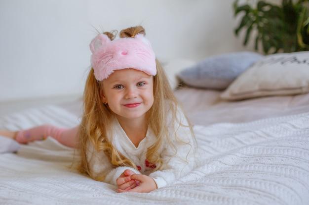 Bambina in pigiama sdraiata sul letto
