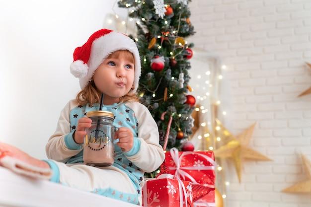 Bambina in pigiama e cappello da babbo natale che beve latte di cacao! l'atmosfera natalizia circonda. scatole da regalo legate con nastri di raso