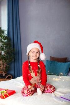 Bambina in pigiama si siede con latte e biscotti di natale