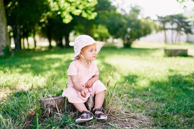 La bambina con un cappello panama si siede su un ceppo su una vista laterale del prato verde