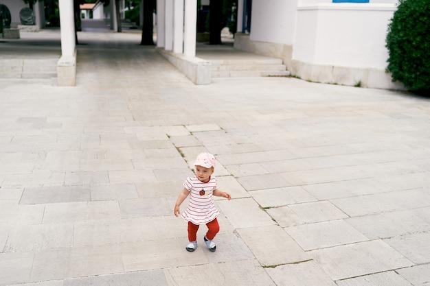 La bambina a panama cammina sulle piastrelle nel cortile del palazzo
