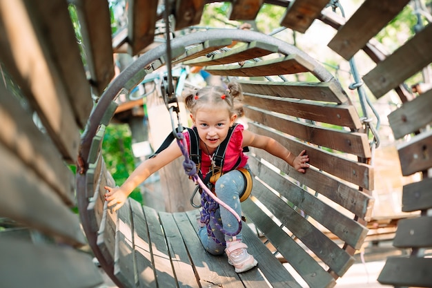 Una bambina supera l'ostacolo nel parco avventura