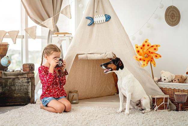 Bambina che fotografa il cane del fox terrier con la macchina fotografica della pellicola all'interno