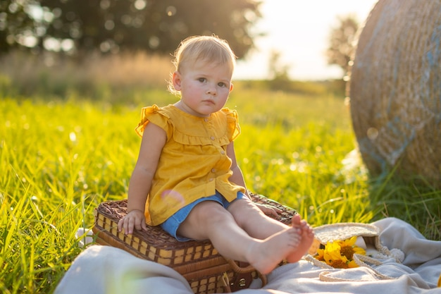 Bambina su un picnic alle luci del tramonto in natura