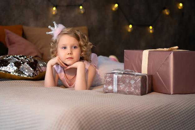 Una bambina con un vestito rosa e una corona sul letto con doni.