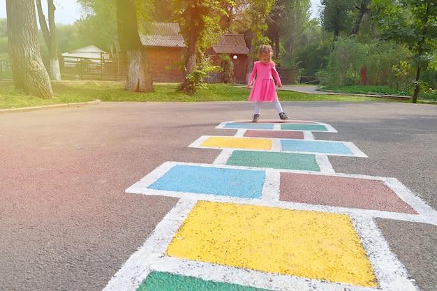 Bambina in un vestito rosa che gioca a campana nel parco giochi all'aperto, attività all'aperto per bambini.