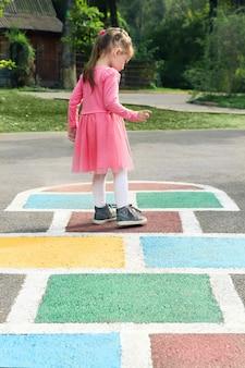 Bambina in un vestito rosa che gioca a campana nel parco giochi all'aperto, attività all'aperto per bambini