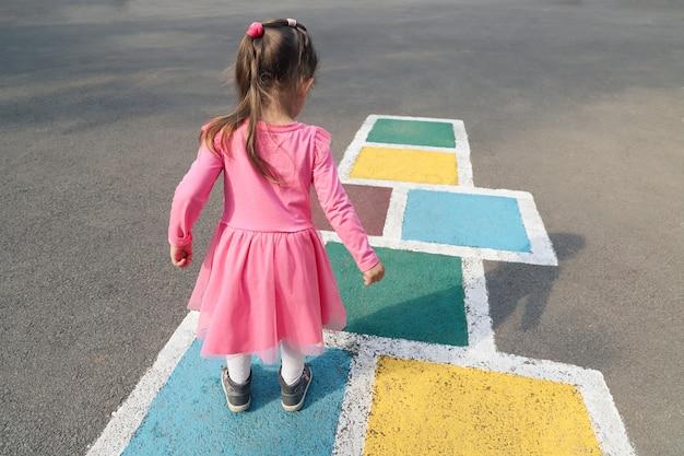La bambina in un vestito rosa gioca a campana per strada.