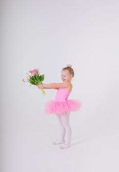 La bambina in un abito rosa con una gonna tutu presenta un mazzo di tulipani su una parete bianca