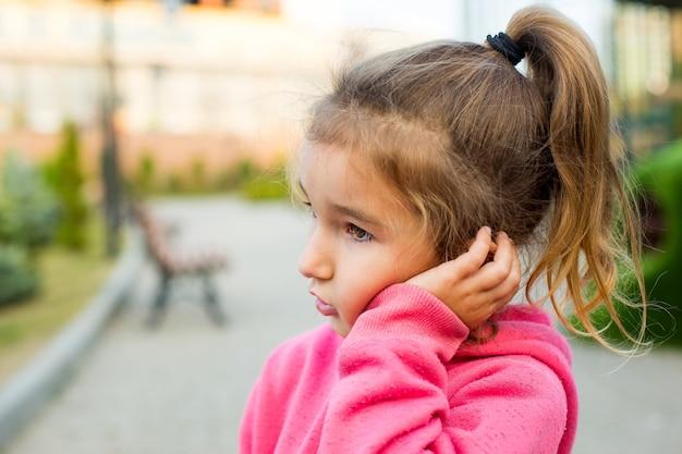Una bambina con una felpa rosa