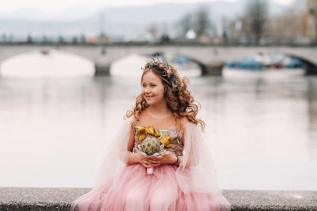 Una bambina in un abito rosa da principessa con un bouquet in mano cammina per la città vecchia di zurigo