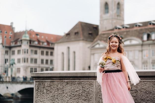 Una bambina vestita da principessa rosa con un bouquet in mano cammina per la città vecchia di zurigo.